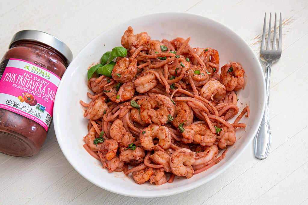 A jar of Primal Kitchen No-Dairy Pink Primavera Sauce is next to a white bowl with hearts of palm pasta, shrimp, and basil covered in pink sauce, with a fork nearby.