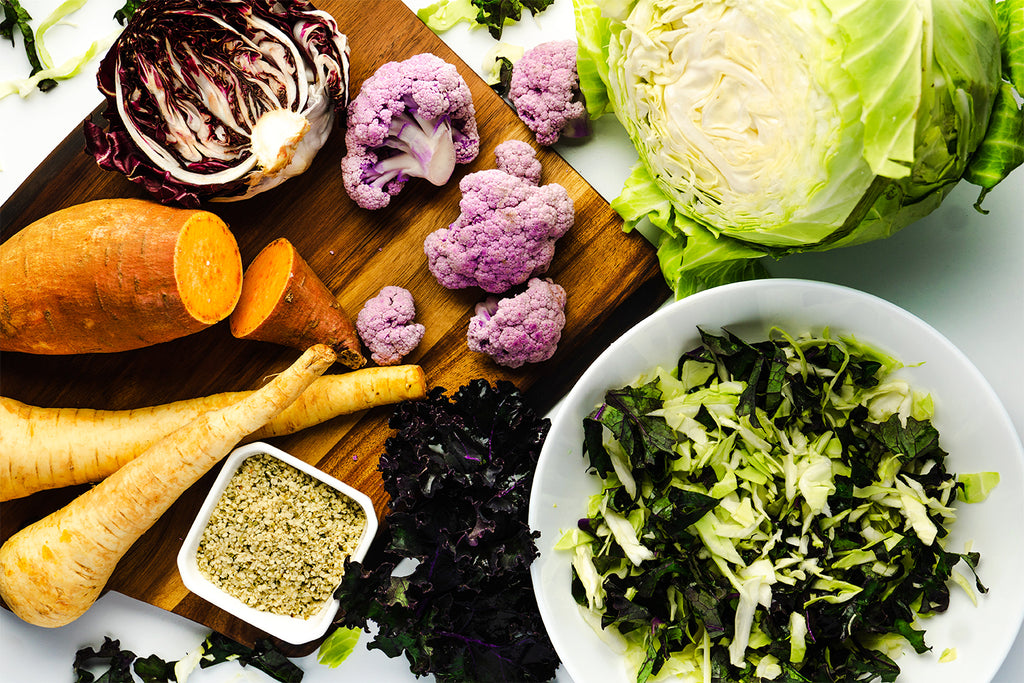 A cutting board includes the ingredients for the roasted vegetable bowl like root vegetables, kale, and hemp seeds.