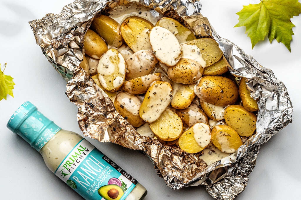 Grilled potatoes in foil are covered in ranch dressing with a bottle of dressing and leaves nearby.