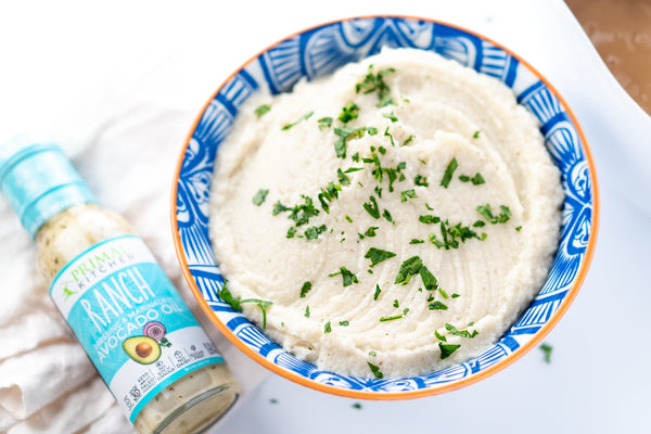 Mashed cauliflower with Ranch Dressing and parsley in a blue bowl