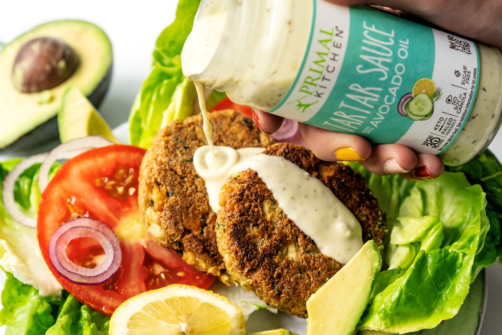 Pouring Primal Kitchen Tartar Sauce on top of keto salmon burgers and a green salad