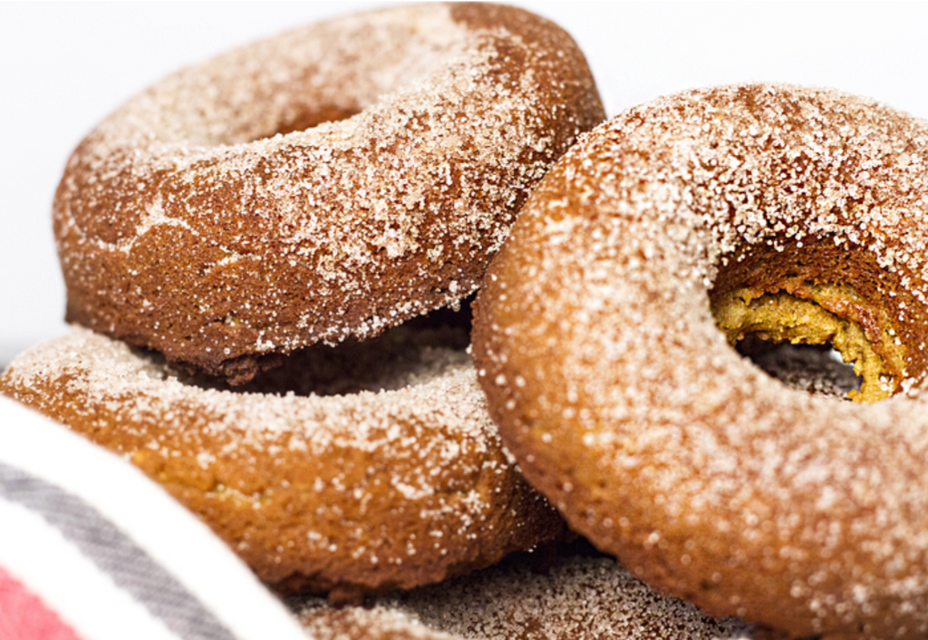 A baked keto donut is rolled in the sweet mixture.