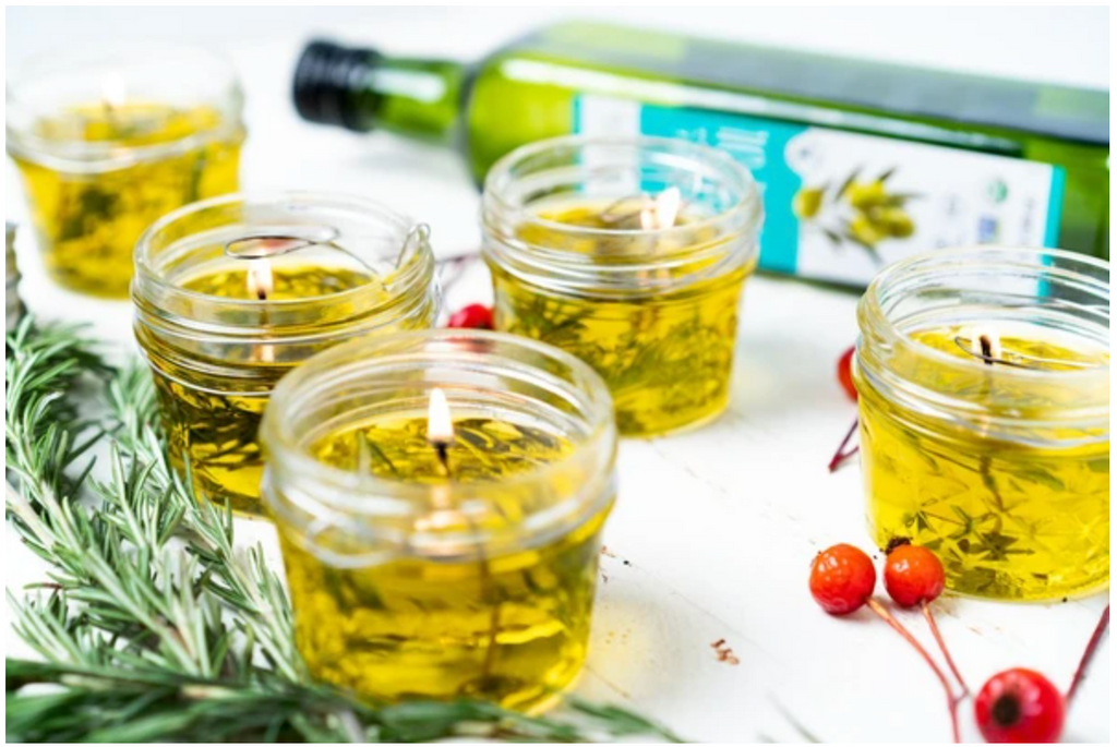 olive oil candles surrounded with berries, greens and olive oil in the background