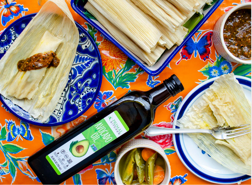 tamale ingredients spread on a colorful tablecloth with avocado oil in the center