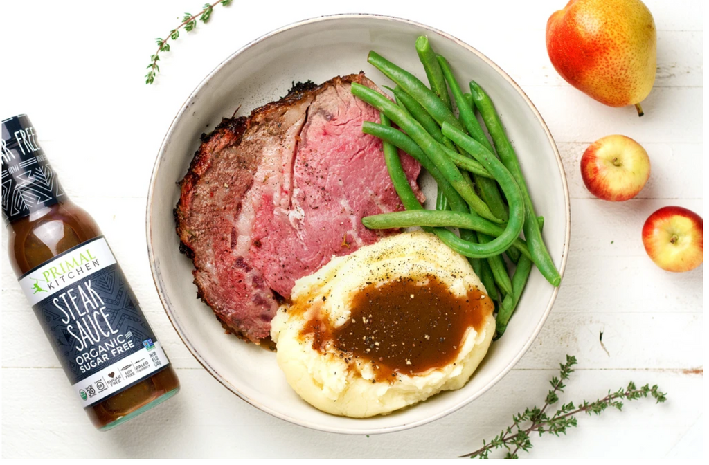steak sauce next to a bowl with sliced prime rib, gravy on mashed potatoes and green beans in a white bowl with pear on the side