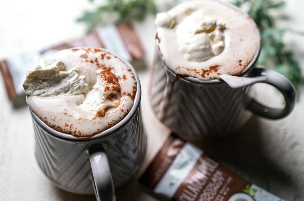 mexican hot chocolate topped with whipped cream in two white mugs surrounded by Collagen Fuel Stick packs in chocolate and tree branches