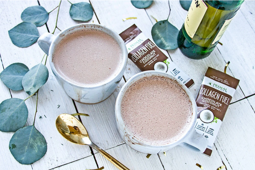 two mugs of hot cocoa surrounded by Collagen Fuel packs, a bottle of liquor, a gold spoon, and eucalyptus branches.