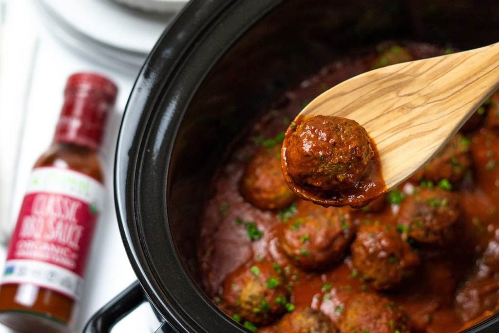 Meatball on a spoon over a slow cooker pot filled with meatballs, next to a bottle of BBQ Sauce