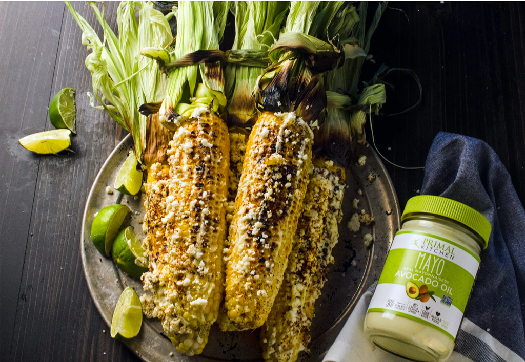 grilled corn stacked on a plate next to mayo