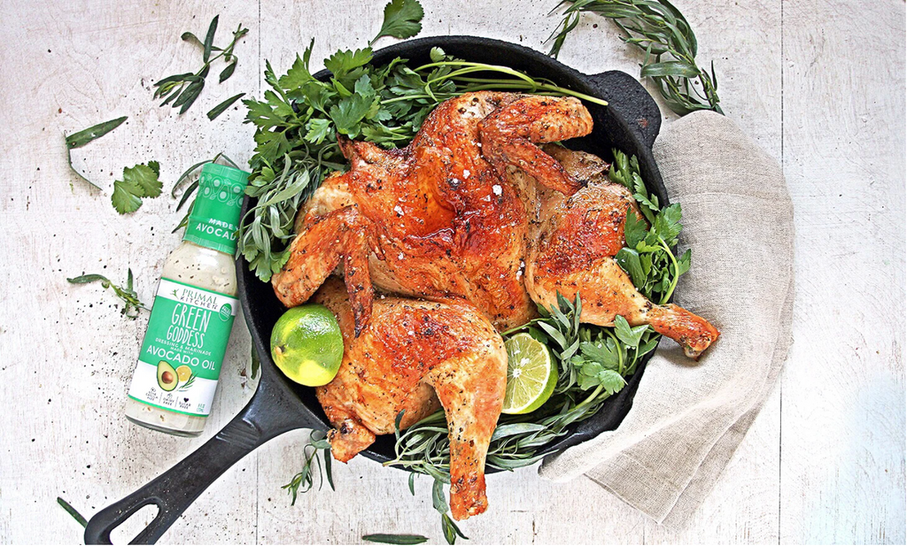 skillet with roasted chiken surrounded by greens and limes, next to a bottle of green goddess dressing.