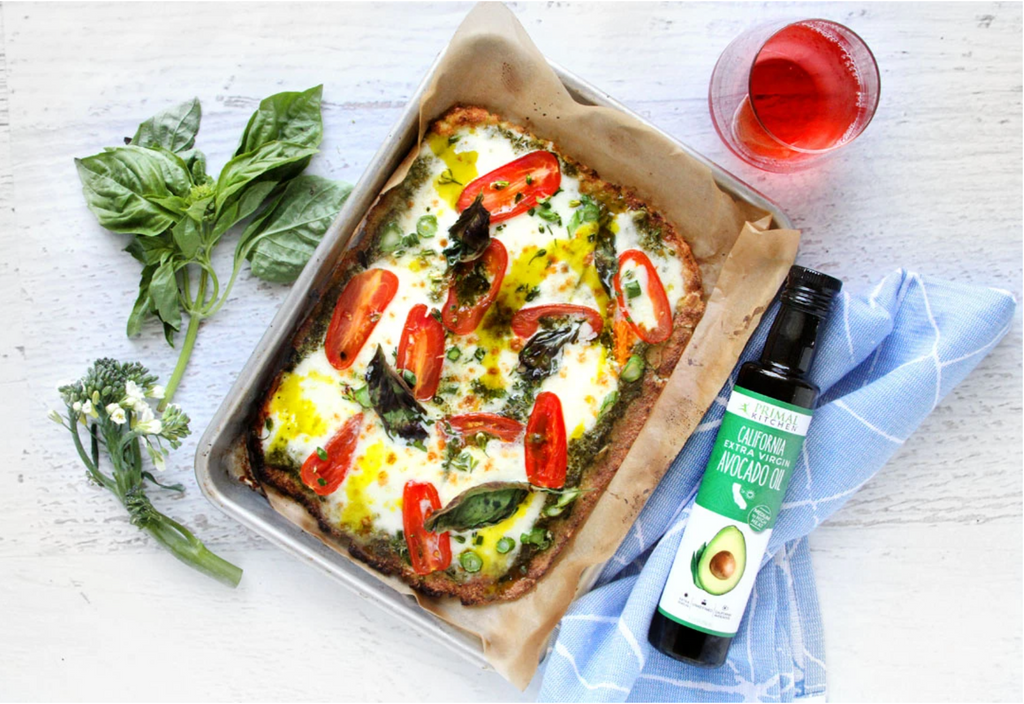 pizza in a square pan, basil on the side, a glass of red wine, and a bottle of Extra Virgin Avocado Oil on a blue dishtowel.