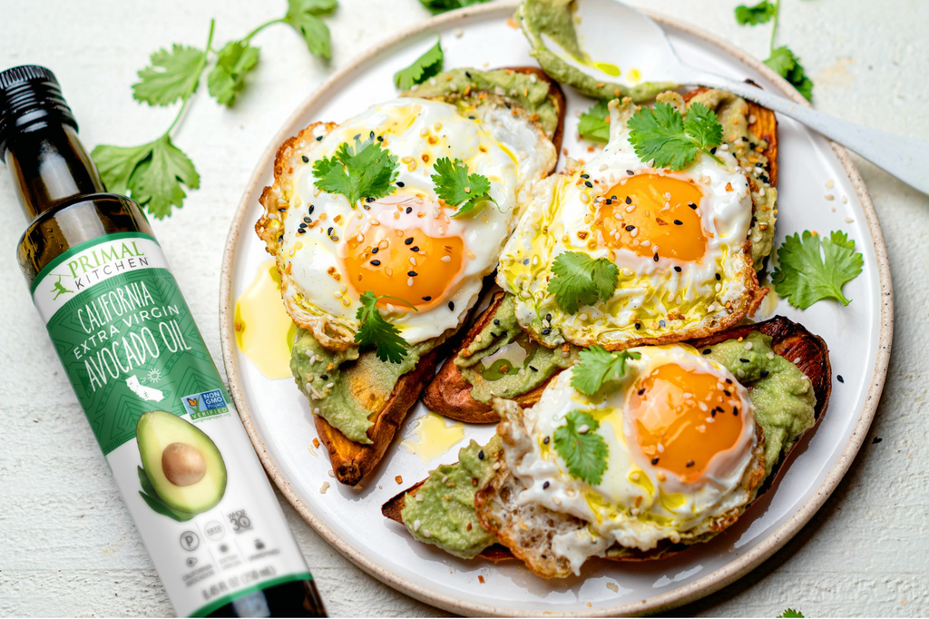 three slices of egg-topped sweet potato toast next to extra virgin avocado oil and greens