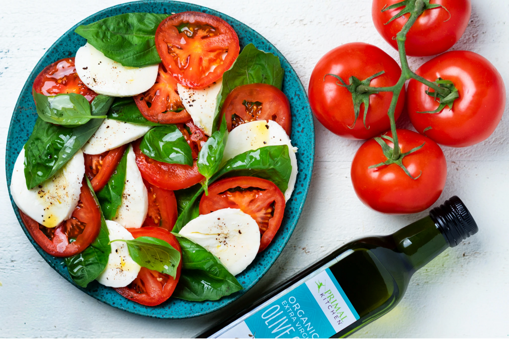 Basil, mozzarella, and tomatoes are layered on a blue plate with 4 tomatoes on a vine and a bottle olive oil nearby.