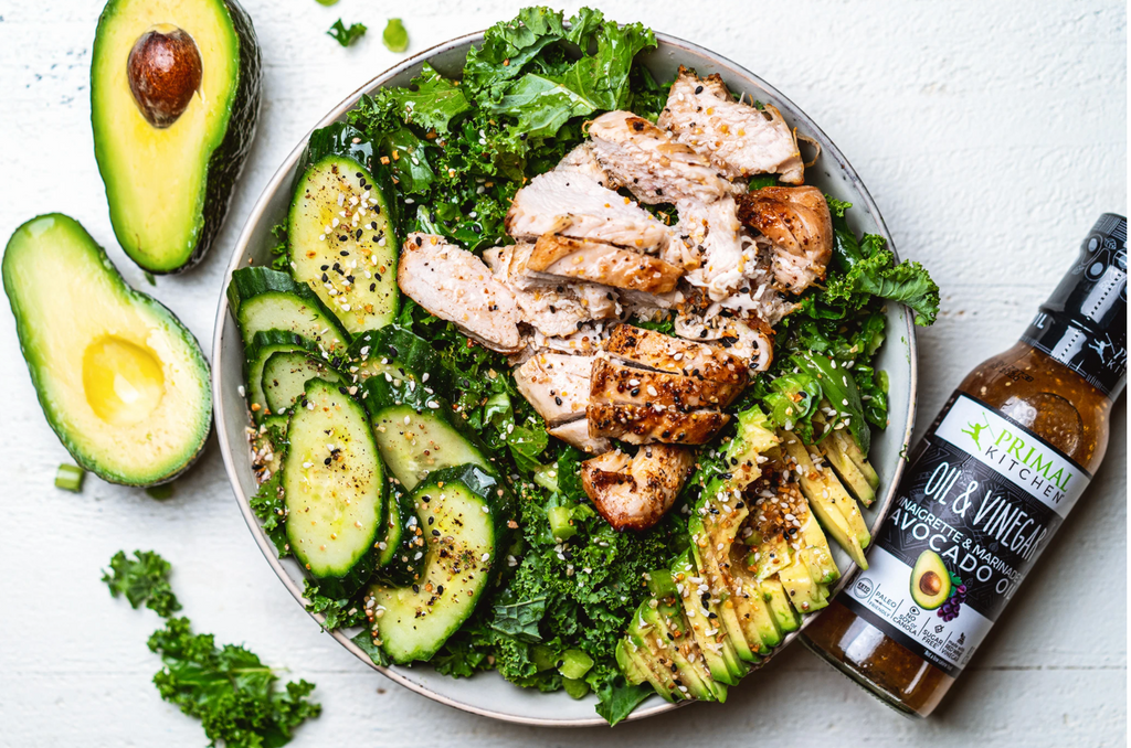Two halves of an avocado sit next to a white plate filled with kale, avocado slices and grilled chicken, and an Oil and Vinegar Dressing bottle lays nearby.