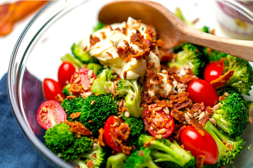 A clear bowl is filled with broccoli florets, red tomatoes, crumbled bacon, and a scoop of cream colored mayo, being stirred by a spoon, on a blue tablecloth.