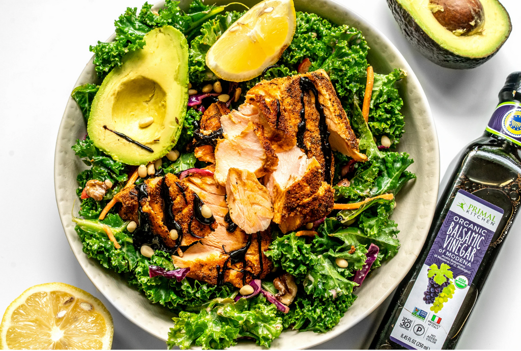 A white bowl, with a half an avocado, half a lemon, and a bottle of Balsamic vinegar next to it, is filled with kale, avocado slices, and sliced salmon.