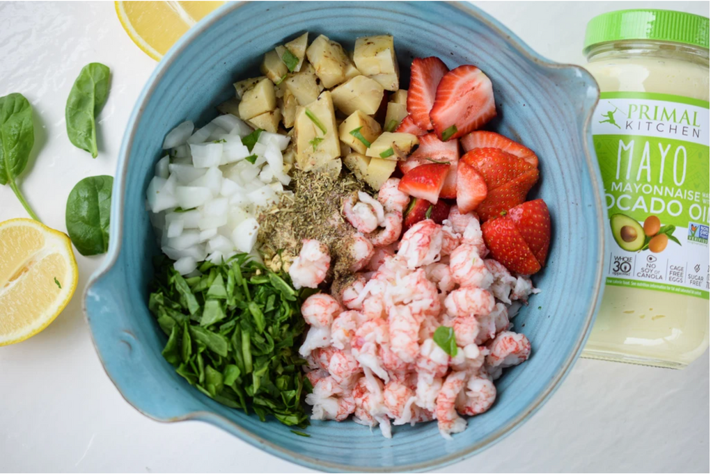 All ingredients for the salad are shown in different sections in a blue bowl, with chopped lemons and greens nearby, as well as a jar of mayo.