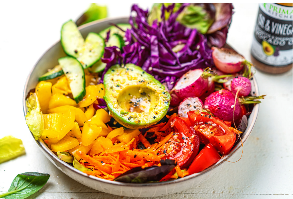 A rainbow plant-based salad sits in a white bowl next to oil and vinegar dressing