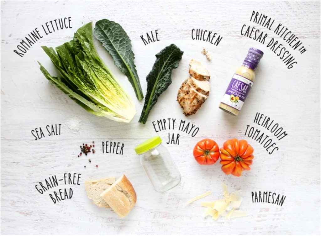 Romaine lettuce, kale, chicken, Caesar dressing, sea salt, a mayo jar, heirloom tomatoes, grain free bread, pepper and parmesan are laid out and labeled on a gray background.