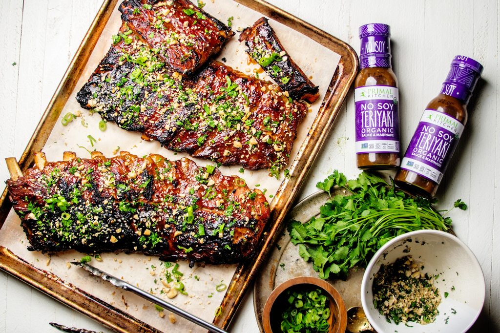 A pan with three pieces of sticky ribs is next to a handful of greens,. spices, and two bottles of No Soy Teriyaki Sauce.