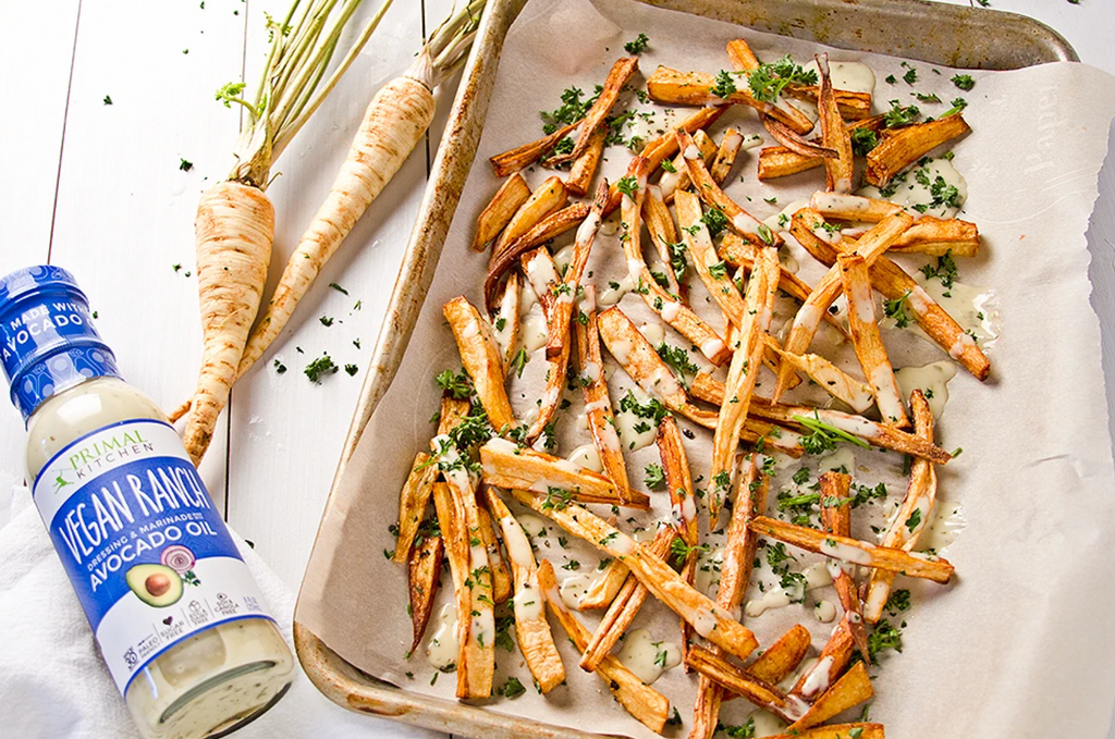 A bottle of vegan ranch lays next two two parsnips, and a tray of parsnip fries on a tray with seasoning.