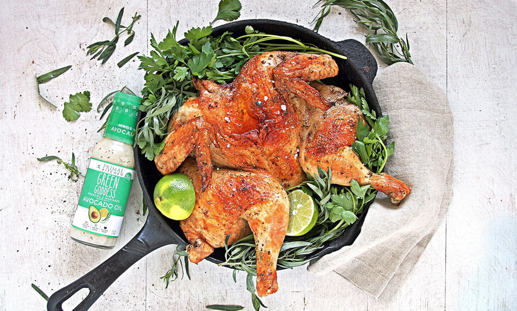 Roasted Chicken sits in a skillet surrounded by greens next to green Goddess dressing
