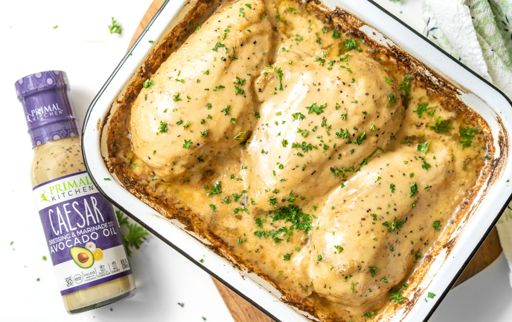 A pan with 3 chicken breasts is covered in Caesar marinade. A bottle of Caesar is next to the pan.