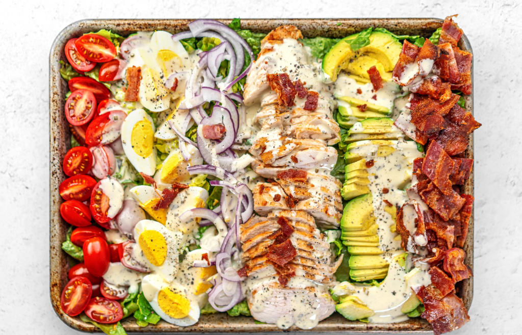 A sheet pan is filled with a Cobb Salad drizzled in Ranch Dressing.