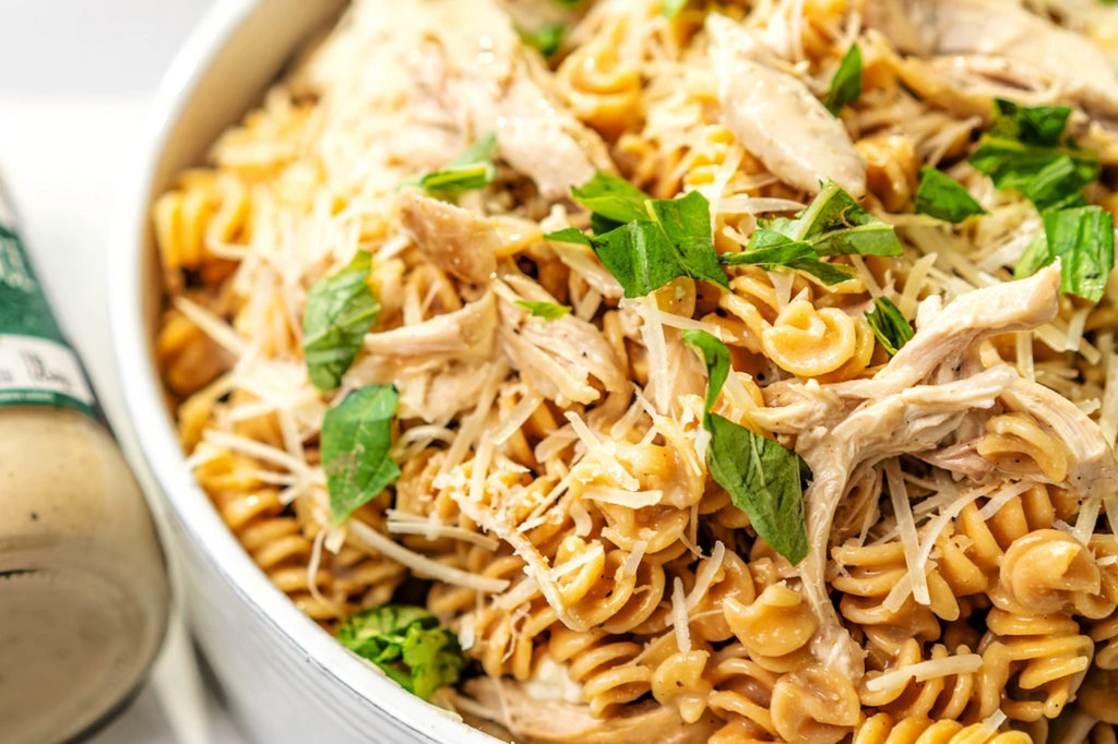 A close-up of gluten-free fusilli topped with greens, rotisserie chicken, and cheese with garlic alfredo sauce nearby.