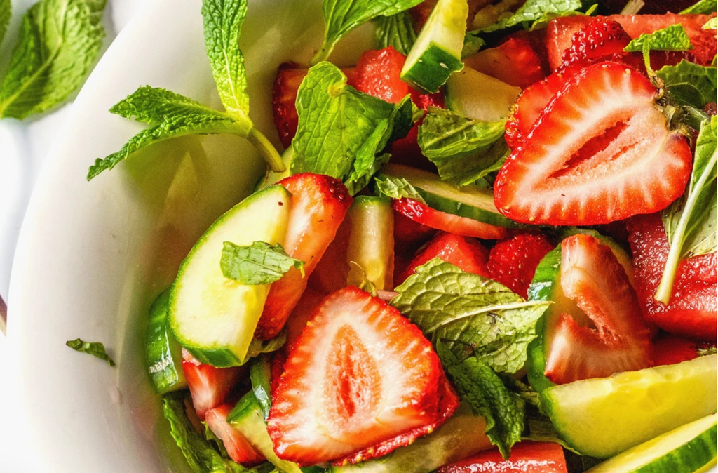 A closeup of strawberries, mint, and lettuce drizzled in Balsamic Dressing.