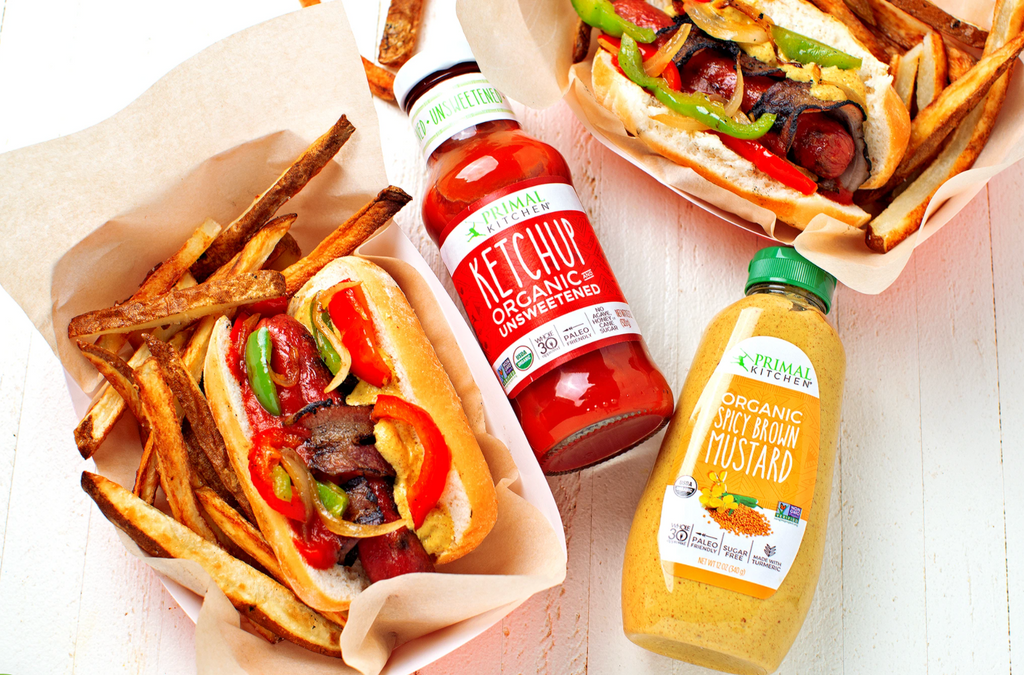 Two bacon wrapped hot dogs with fries and sliced veggies on top, with ketchup and mustard bottles between them.
