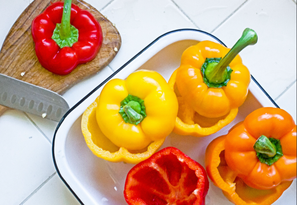 Sliced bell peppers (orange, yellow and red) is on a white dish.