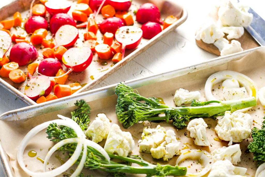 Two silver baking trays with assorted vegetables on parchment paper are next to each other.