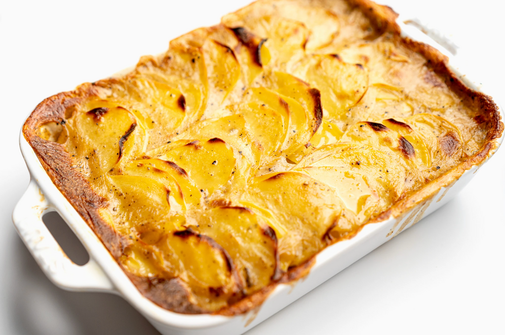 Vegan scalloped potatoes are cooked in a white dish.