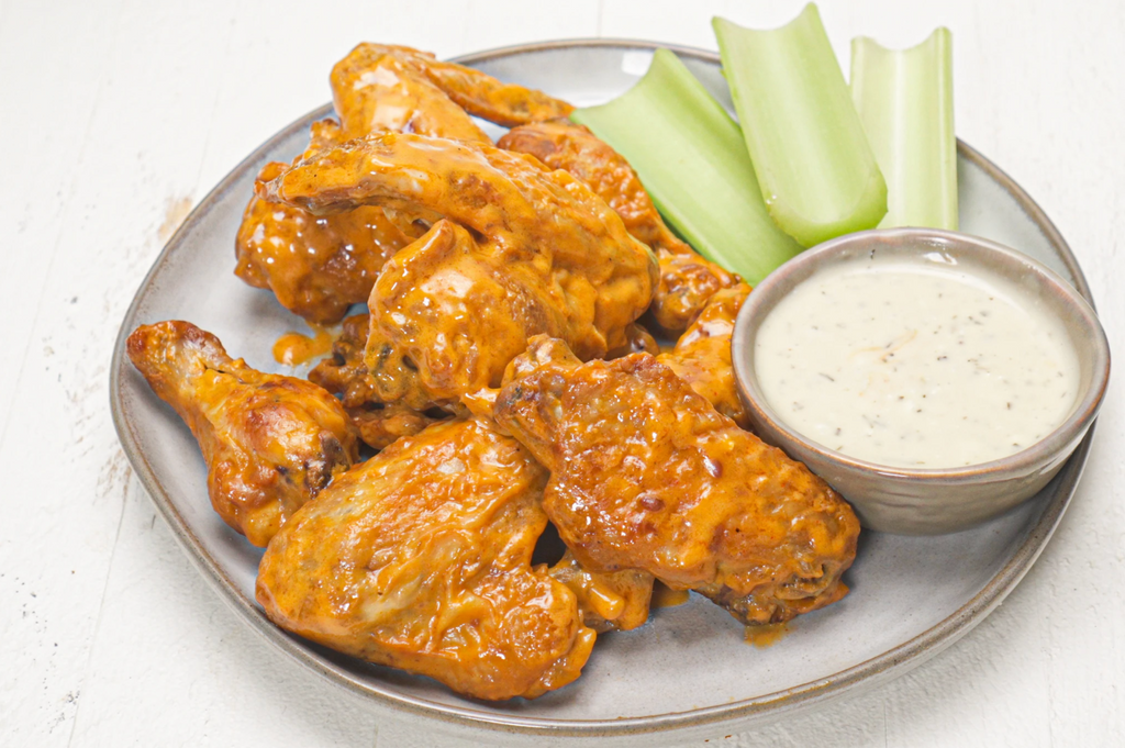 Buffalo Sauce wings are on a plate with ranch and celery.