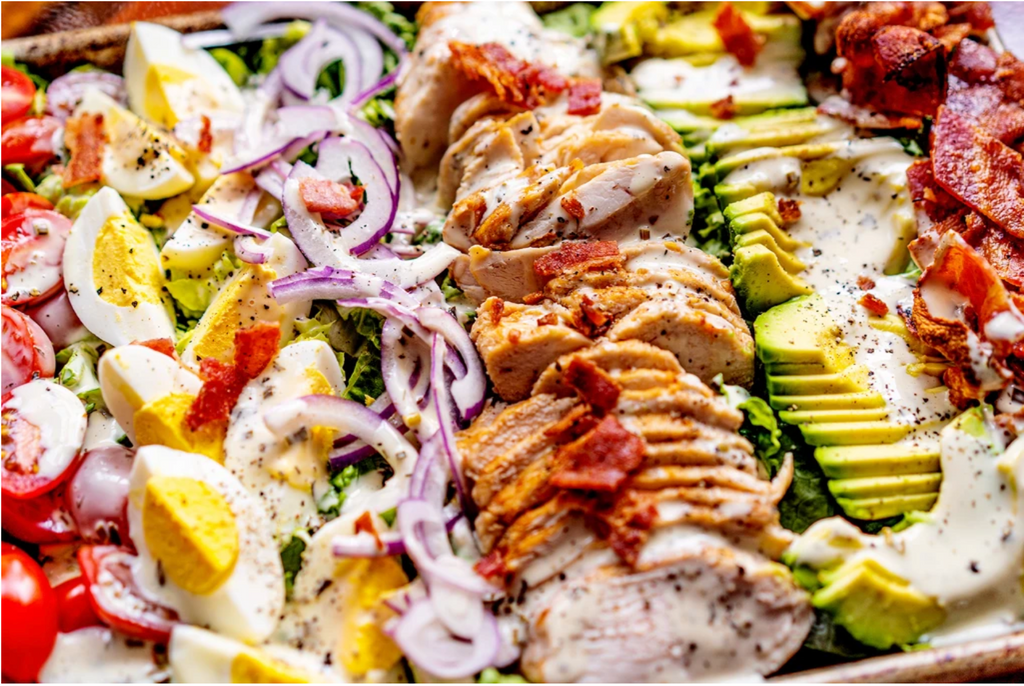 A close-up of the Keto Cobb Salad drizzled in Ranch dressing, pictured in a pan.