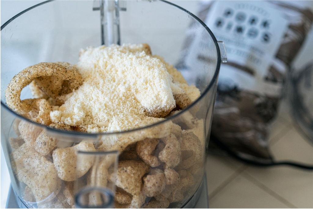 Pork rinds are in a blender, preparing to make the topping of this Keto Parmeasan Chicken.