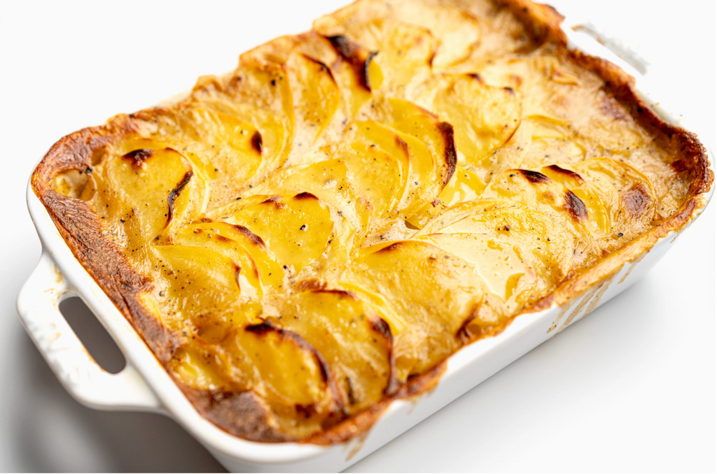 Vegan scalloped potatoes are baked in a white casserole dish.