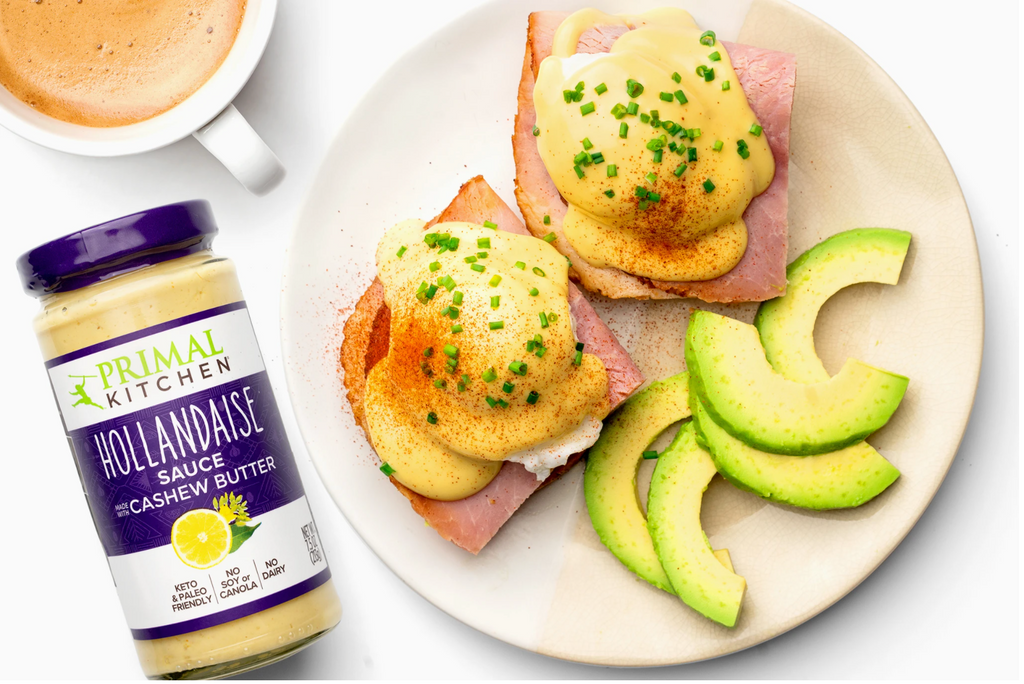 Keto eggs benedict is served with avocado slices and coffee.