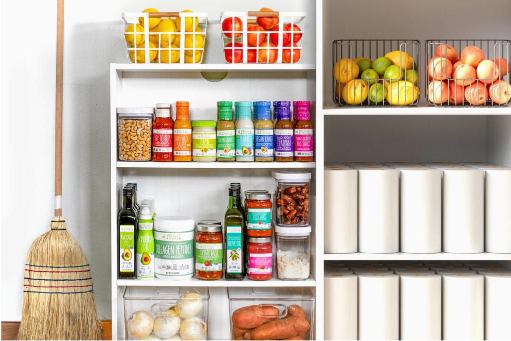A pantry is filled with Primal Kitchen products and cleaning supplies in white shelves.