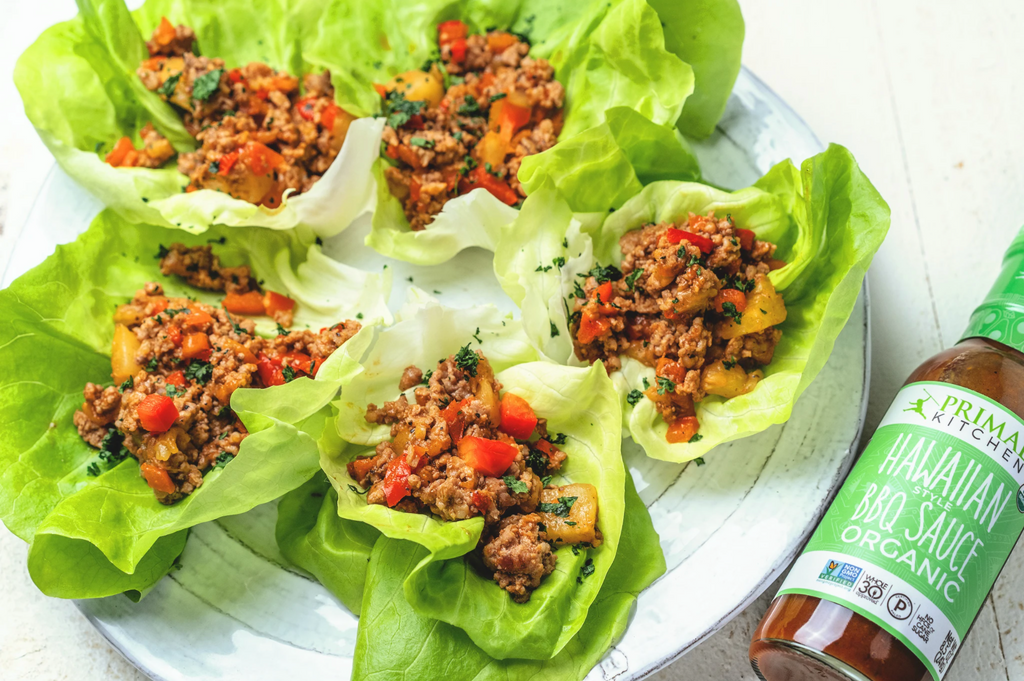 Whole30 Lettuce cups are arranged on a white plate with Hawaiian Style BBQ next to it.