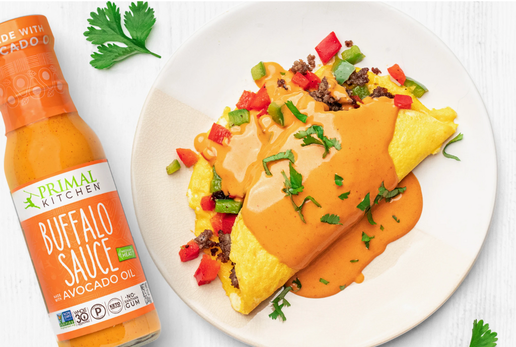 A Southwest omelet is drizzled in Buffalo Sauce with the bottle next to it.