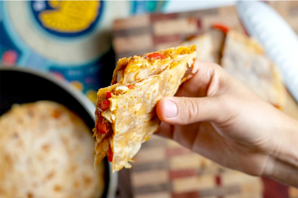 A hand holds a bbq chicken quesadilla over the ingredients.