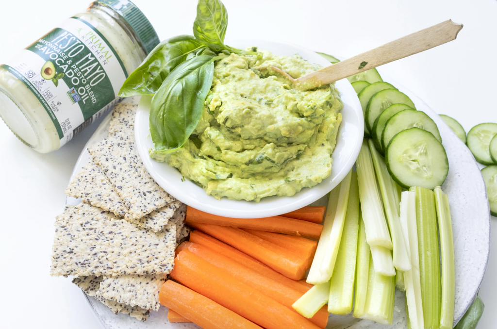 Creamy guacamole is surrounded by crudité and pesto mayo in the background.