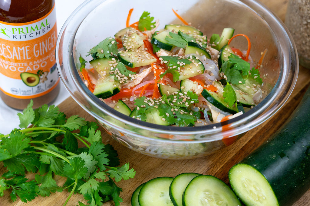 Cold sesame noodles in a clear bowl next to cilantro, sliced cucumber, and Primal Kitchen Sesame Ginger Dressing