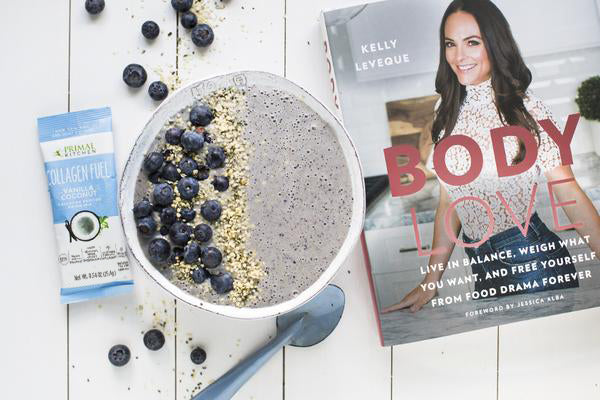Kelly LeVeque's blueberry muffin smoothie bowl next to Primal Kitchen Collagen Fuel Vanilla and Kelly's Body Love book