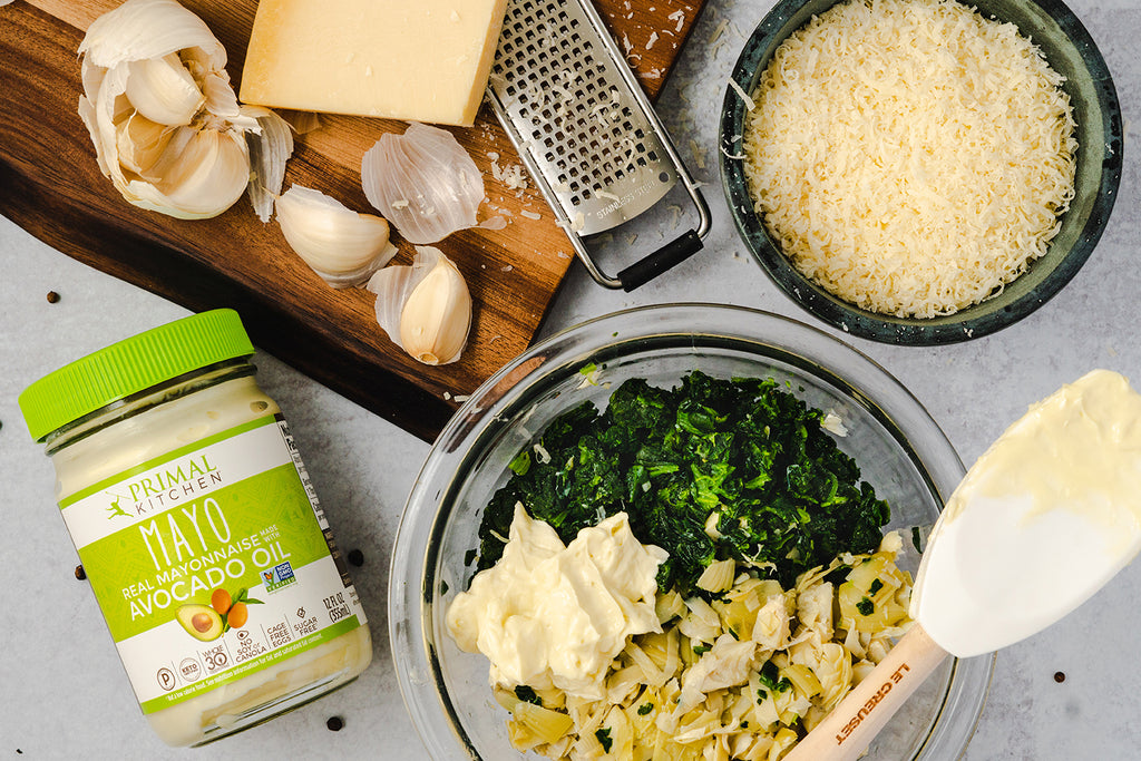 Spinach artichoke dip ingredients: garlic cloves, a block of parmesan cheese on top of a grater, a bowl of grated parmesan cheese, a mixing bowl with chopped spinach, chopped artichokes, and mayo. A jar of Primal Kitchen Mayo next to the mixing bowl.