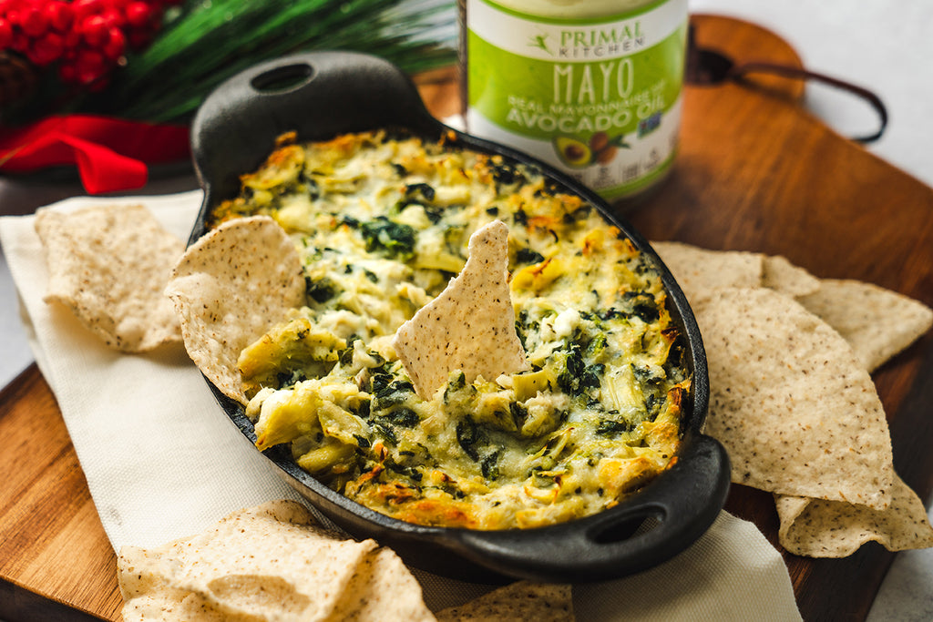 Spinach artichoke dip, baked, in a cast iron skillet with tortilla chips sticking out. More tortilla chips on the side next to Primal Kitchen Mayo.