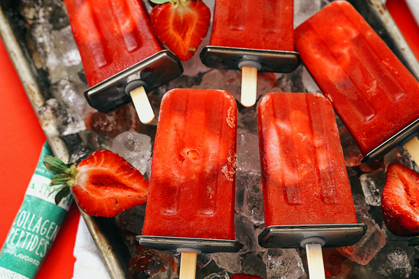 Close up of Strawberry Orange Collagen Pops on a tray with ice cubes and sliced strawberries