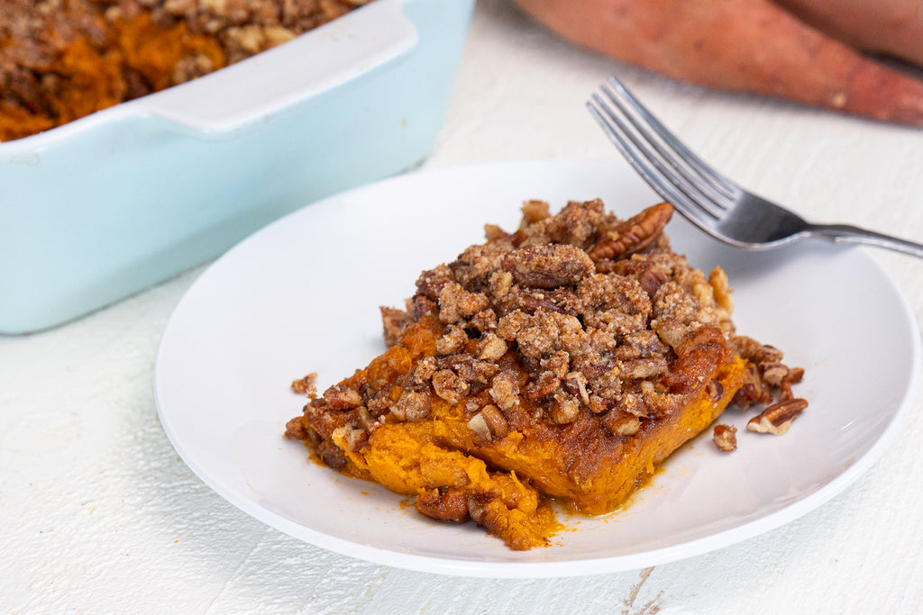 Serving of sweet potato casserole on a white plate with a silver fork